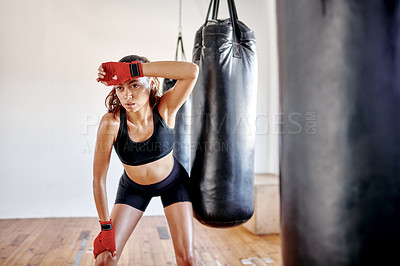 Buy stock photo Cropped shot of an attractive young female boxer looking exhausted while taking a break in a gym