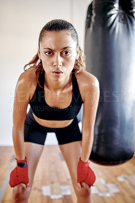 Buy stock photo Cropped portrait of an attractive young female boxer looking exhausted while taking a break in a gym