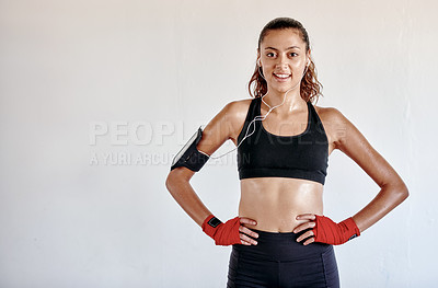 Buy stock photo Cropped portrait of an attractive young female boxer listening to music on her cellphone while standing in a gym