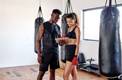 Buy stock photo Cropped shot of an attractive young female boxer using a digital tablet with her fitness coach in a gym