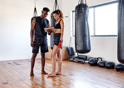 Buy stock photo Full length shot of an attractive young female boxer using a digital tablet with her fitness coach in a gym
