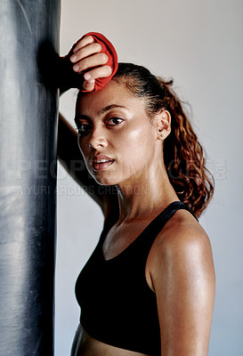 Buy stock photo Cropped portrait of an attractive young female boxer leaning on a punching bag while taking a break in a gym