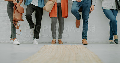 Buy stock photo Cropped shot of a group of businesspeople lined up against a wall