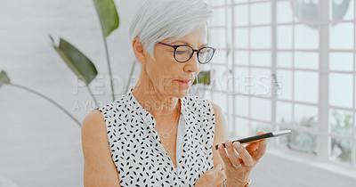 Buy stock photo Shot of a confident senior businesswoman using a smartphone and earphones in a modern office