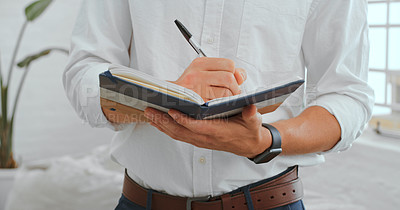 Buy stock photo Cropped shot of a businessman writing in a notebook in a modern office