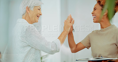 Buy stock photo Shot of two businesswomen giving each other a high five in a modern office