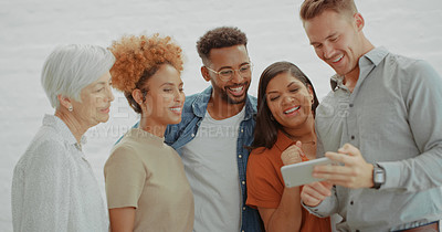 Buy stock photo Shot of a group of diverse businesspeople using a smartphone together in a modern office