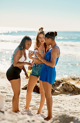 Buy stock photo Shot of three young women looking at something on a cellphone while on the beach