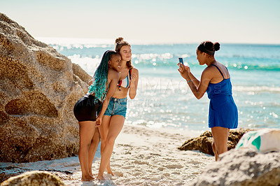 Buy stock photo Shot of a young woman taking a selfie of her two female friends at the beach