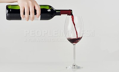 Buy stock photo Cropped shot of an unrecognizable woman standing and pouring a bottle of red wine into a glass in the studio
