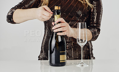 Buy stock photo Cropped shot of an unrecognizable woman using a cork screw to open a bottle of champagne in the studio
