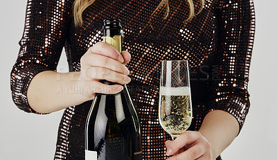 Buy stock photo Cropped shot of an unrecognizable woman standing with a bottle of champagne and a glass in the studio