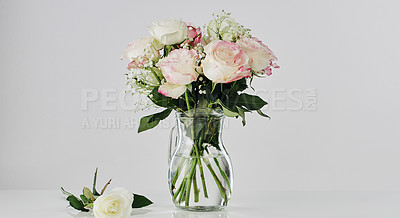 Buy stock photo Cropped shot of a bouquet of roses in a vase on the tabletop in an empty studio
