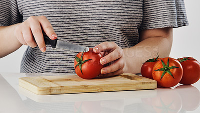 Buy stock photo Cropped shot of an unrecognizable woman cutting tomatoes on a wooden board the studio during the day