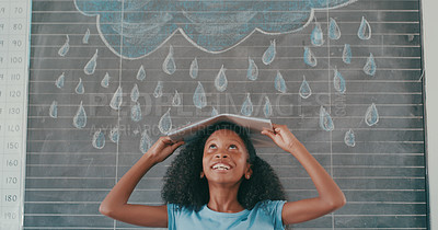 Buy stock photo Shot of a young schoolgirl covering herself with a book in front of rain drawn on a black board