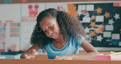 Buy stock photo Shot of a young girl doing schoolwork in a classroom