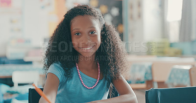 Buy stock photo Portrait of a happy young girl sitting at her desk in a classroom