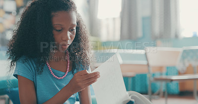 Buy stock photo Shot of a young girl reading a book at school