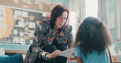 Buy stock photo Shot of a teacher reading a book to a young girl at school