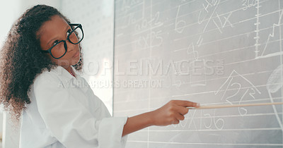 Buy stock photo Shot of a young girl solving a maths equation on a chalkboard at school