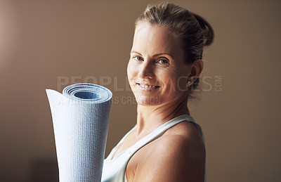 Buy stock photo Cropped portrait of an attractive young woman standing alone and holding her yoga mat before an indoor yoga session