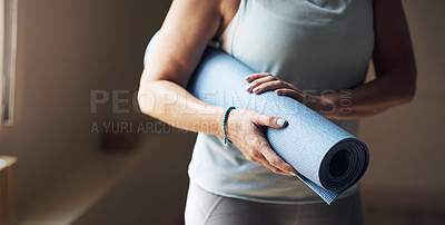 Buy stock photo Cropped shot of an unrecognizable woman standing alone and holding her yoga mat before an indoor yoga session