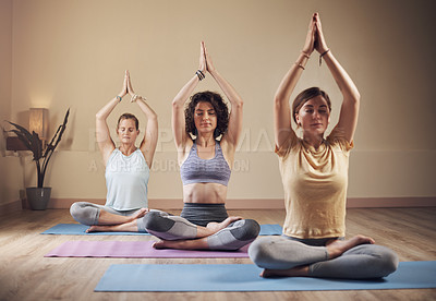 Buy stock photo Full length shot of a young group of women sitting together and meditating after an indoor yoga session