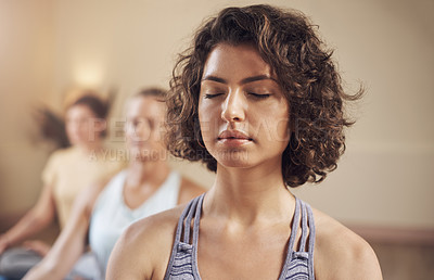 Buy stock photo Cropped shot of a young group of women sitting together and meditating after an indoor yoga session