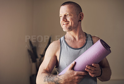 Buy stock photo Cropped shot of a handsome young man standing alone and holding his yoga mat before an indoor yoga session