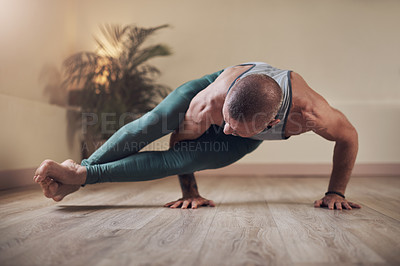Buy stock photo Full length shot of a handsome young man holding an eight angle pose during an indoor yoga session alone