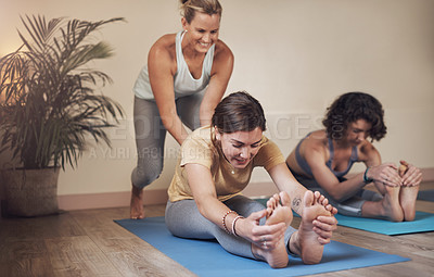 Buy stock photo Full length shot of an attractive young yoga instructor helping her clients during an indoor yoga session