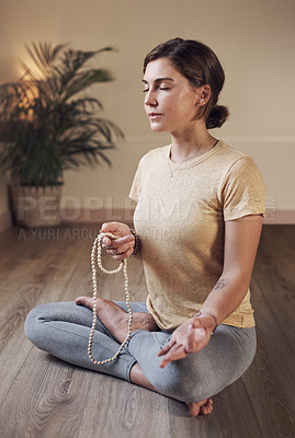 Buy stock photo Full length shot of an attractive young woman sitting indoors and using mala beads during her meditation routine