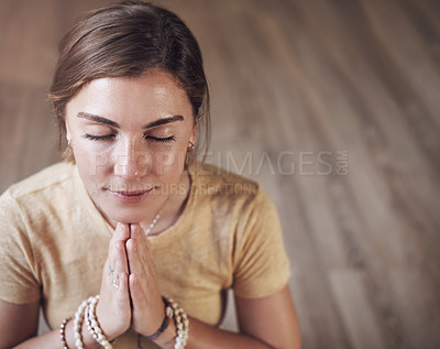 Buy stock photo Cropped shot of an attractive young woman sitting indoors and using mala beads during her meditation routine