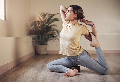 Buy stock photo Full length shot of an attractive young woman holding a mermaid's pose during an indoor yoga session alone