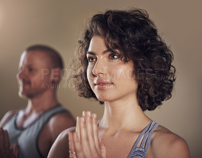 Buy stock photo Cropped shot of two young yogis standing together and meditating with their palms together after an indoor yoga session