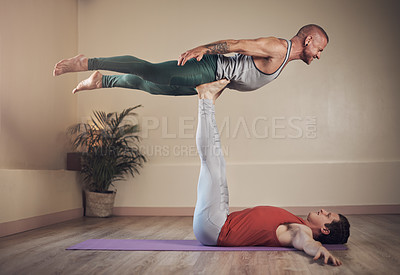 Buy stock photo Full length shot of a handsome young man doing acro yoga with his partner in a yoga studio