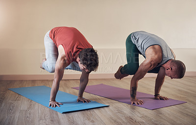 Buy stock photo Full length shot of two young men holding a crane pose during an indoor yoga session together