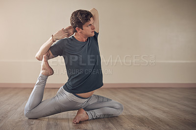Buy stock photo Full length shot of a handsome young man holding a mermaid's pose during an indoor yoga session alone