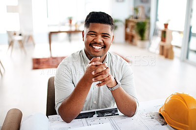Buy stock photo Shot of a young businessman working on a blueprint in a modern office