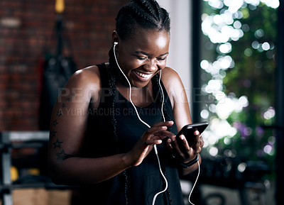 Buy stock photo Cropped shot of an attractive young female athlete listening to music while standing in the gym