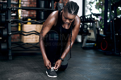 Buy stock photo Full length shot of an attractive young female athlete tying her laces before a workout in the gym