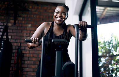 Buy stock photo Cropped portrait of an attractive young female athlete working out on an elliptical machine in the gym