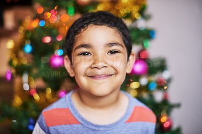 Buy stock photo Portrait of a cheerful little boy smiling at the camera with a Christmas tree in the background at home during the day