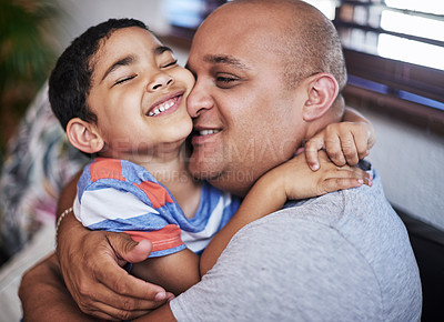 Buy stock photo Cropped shot of a cheerful young man hugging his son while being seated on a sofa at home during the day