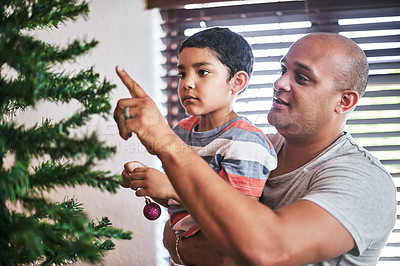 Buy stock photo Cropped shot of a cheerful young man and his son putting up Christmas decorations on a tree at home during the day