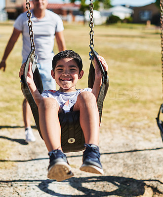 Buy stock photo Portrait of a cheerful little boy swinging on a swing outside in a park during the day