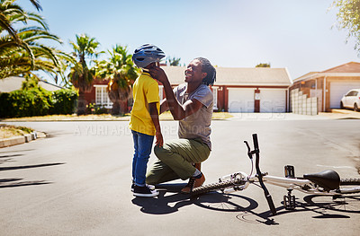 Buy stock photo Full length shot of an affectionate young single father adjusting his son's helmet before he rides a bike outdoors