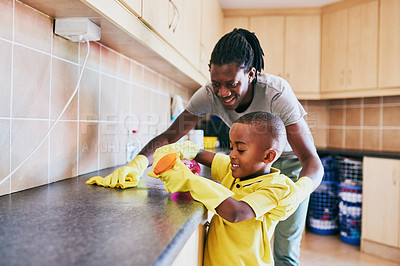 Buy stock photo Cropped shot of an adorable little boy assisting his dad with cleaning the kitchen at home