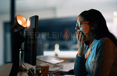 Buy stock photo Shot of a young businesswoman yawning while working on a computer in an office at night