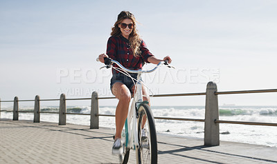 Buy stock photo Shot of a beautiful woman out on the promenade with her bicycle
